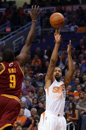 Mar 12, 2014; Phoenix, AZ, USA; Phoenix Suns forward Marcus Morris (15) shoots the ball against Cleveland Cavaliers forward Luol Deng (9) in the second half at US Airways Center. The Cavaliers won 110-101.  Mandatory Credit: Jennifer Stewart-USA TODAY Sports