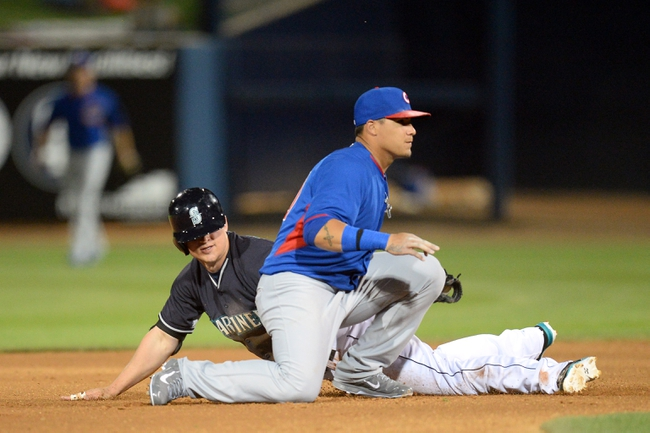 Mar 12, 2014; Peoria, AZ, USA; Seattle Mariners third baseman Kyle Seager (15) beats a throw to Chicago Cubs shortstop Javier Baez (70) to steal second base at Peoria Sports Complex. Mandatory Credit: Joe Camporeale-USA TODAY Sports