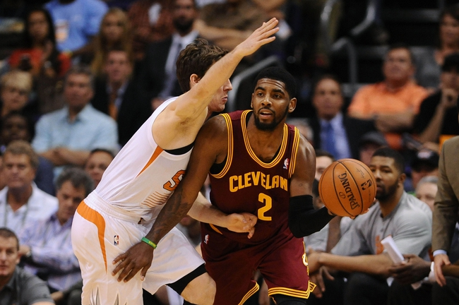 Mar 12, 2014; Phoenix, AZ, USA; Cleveland Cavaliers guard Kyrie Irving (2) handles the ball against the Phoenix Suns guard Goran Dragic (1) in the second half at US Airways Center. The Cavaliers won 110-101.  Mandatory Credit: Jennifer Stewart-USA TODAY Sports