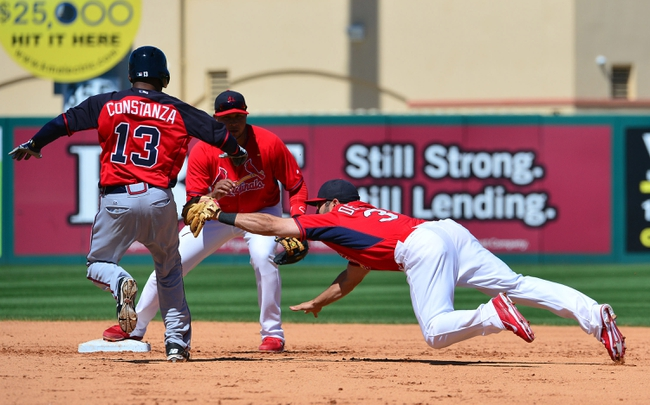 Mar 13, 2014; Jupiter, FL, USA; St. Louis Cardinals shortstop Daniel Descalso (33) makes a diving tag on Atlanta Braves left fielder Jose Constanza (13) at Roger Dean Stadium. The Cardinals defeated the Braves 11-0. Mandatory Credit: Scott Rovak-USA TODAY Sports