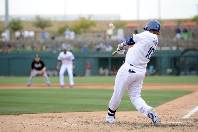 Mar 13, 2014; Phoenix, AZ, USA; Los Angeles Dodgers second baseman Justin Turner (10) hits a sacrifice fly in the fourth inning of a spring training game against the Cincinnati Reds at Camelback Ranch. Mandatory Credit: Joe Camporeale-USA TODAY Sports