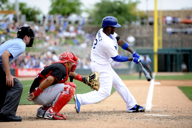 Mar 13, 2014; Phoenix, AZ, USA; Los Angeles Dodgers shortstop Hanley Ramirez (13) hits a solo home run in the fifth inning of a spring training game against the Cincinnati Reds at Camelback Ranch. Mandatory Credit: Joe Camporeale-USA TODAY Sports