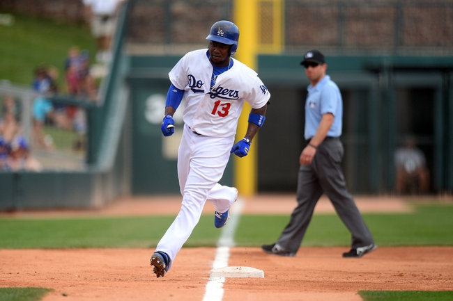 Mar 13, 2014; Phoenix, AZ, USA; Los Angeles Dodgers shortstop Hanley Ramirez (13) rounds third base and heads home after hitting a solo home run against the Cincinnati Reds during a spring training game at Camelback Ranch. Mandatory Credit: Joe Camporeale-USA TODAY Sports