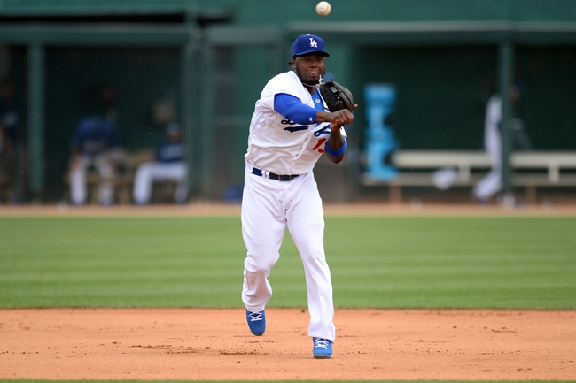 Mar 13, 2014; Phoenix, AZ, USA; Los Angeles Dodgers shortstop Hanley Ramirez (13) throws out a Cincinnati Reds runner at first base in the seventh inning of a spring training game at Camelback Ranch. Mandatory Credit: Joe Camporeale-USA TODAY Sports