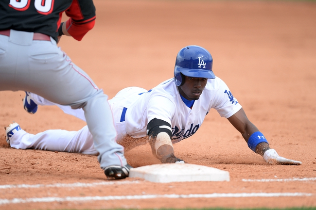 Mar 13, 2014; Phoenix, AZ, USA; Los Angeles Dodgers shortstop Dee Gordon (9) dives back to first base during a pickoff attempt in the seventh inning of a spring training game against the Los Angeles Dodgers at Camelback Ranch. Mandatory Credit: Joe Camporeale-USA TODAY Sports