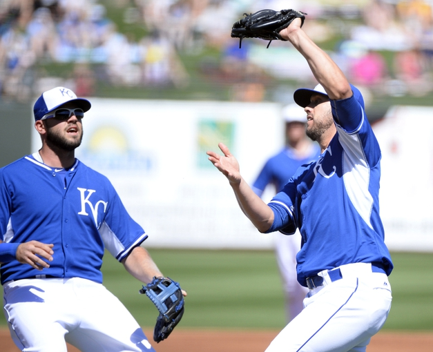 Mar 15, 2014; Surprise, AZ, USA; Kansas City Royals pitcher James Shileds (33) makes a catch in front of third baseman Mike Moustakas (8) for the final out of the first inning against the Chicago Cubs at Surprise Stadium. Mandatory Credit: Christopher Hanewinckel-USA TODAY Sports