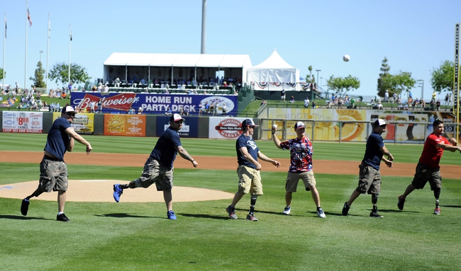 Mar 15, 2014; Surprise, AZ, USA; Members of the Wounded Warrior Softball Team throw out the honorary first pitch prior to the Kansas City Royals game against the Chicago Cubs at Surprise Stadium. Mandatory Credit: Christopher Hanewinckel-USA TODAY Sports