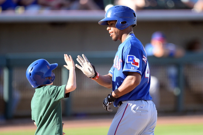 Mar 15, 2014; Phoenix, AZ, USA; Texas Rangers outfielder Nick Williams slaps hands with a bat boy after hitting a home run in the ninth inningagainst the Oakland Athletics at Phoenix Municipal Stadium. The Rangers won 16-15. Mandatory Credit: Joe Camporeale-USA TODAY Sports