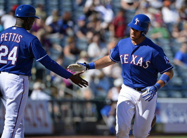 Mar 16, 2014; Surprise, AZ, USA; Texas Rangers catcher J.P. Arencibia (7) is congratulated by third base coach Gary Pettis (24) after a grand slam during the sixth inning against the Chicago White Sox at Surprise Stadium. Mandatory Credit: Christopher Hanewinckel-USA TODAY Sports