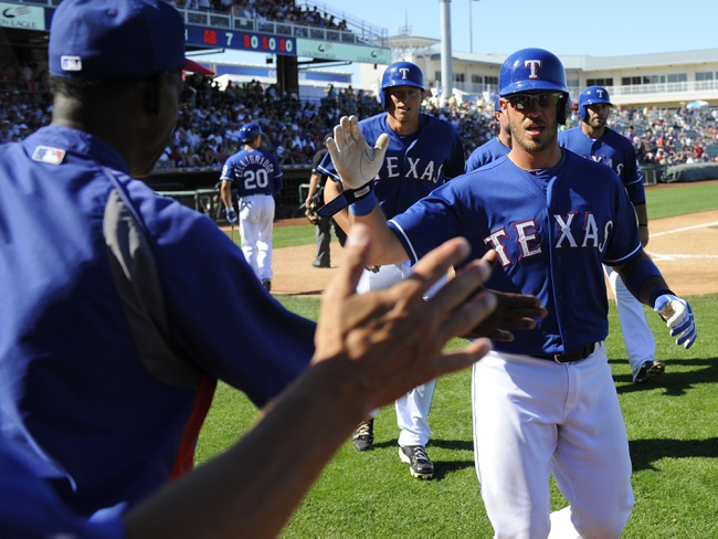 Mar 16, 2014; Surprise, AZ, USA; Texas Rangers catcher J.P. Arencibia (7) is congratulated by teammates after a grand slam during the sixth inning against the Chicago White Sox at Surprise Stadium. Mandatory Credit: Christopher Hanewinckel-USA TODAY Sports