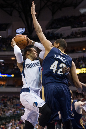 Feb 26, 2014; Dallas, TX, USA; New Orleans Pelicans center Alexis Ajinca (42) defends against Dallas Mavericks shooting guard Monta Ellis (11) during the game at the American Airlines Center. The Mavericks defeated the Pelicans 108-89. Mandatory Credit: Jerome Miron-USA TODAY Sports