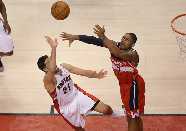 Feb 27, 2014; Toronto, Ontario, CAN; Washington Wizards guard Bradley Beal (3) defends against Toronto Raptors guard Greivis Vasquez (21) at Air Canada Centre. The Wizards beat the Raptors 134-129 in triple overtime. Mandatory Credit: Tom Szczerbowski-USA TODAY Sports