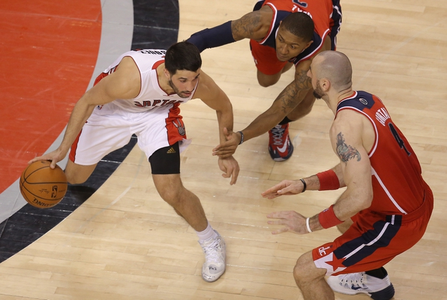 Feb 27, 2014; Toronto, Ontario, CAN; Toronto Raptors guard Greivis Vasquez (21) is guarded as he dribbles by Washington Wizards center Marcin Gortat (4) and guard Bradley Beal (3) at Air Canada Centre. The Wizards beat the Raptors 134-129 in triple overtime. Mandatory Credit: Tom Szczerbowski-USA TODAY Sports