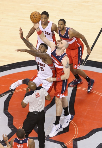 Feb 27, 2014; Toronto, Ontario, CAN; Washington Wizards center Marcin Gortat (4) wins a tip-off against Toronto Raptors forward Amir Johnson (15) in overtime at Air Canada Centre. The Wizards beat the Raptors 134-129 in triple overtime. Mandatory Credit: Tom Szczerbowski-USA TODAY Sports