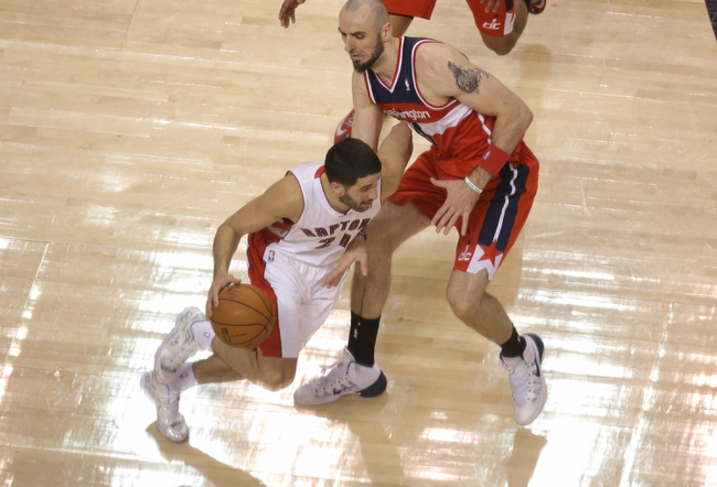 Feb 27, 2014; Toronto, Ontario, CAN; Toronto Raptors guard Greivis Vasquez (21) dribbles as Washington Wizards center Marcin Gortat (4) plays defense at Air Canada Centre. The Wizards beat the Raptors 134-129 in triple overtime. Mandatory Credit: Tom Szczerbowski-USA TODAY Sports