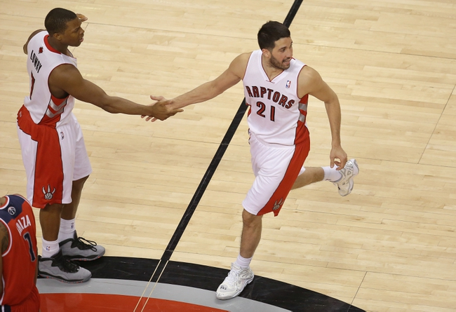 Feb 27, 2014; Toronto, Ontario, CAN; Toronto Raptors guard Greivis Vasquez (21) is congratulated by point guard Kyle Lowry (7) after scoring a basket against the Washington Wizards at Air Canada Centre. The Wizards beat the Raptors 134-129 in triple overtime. Mandatory Credit: Tom Szczerbowski-USA TODAY Sports