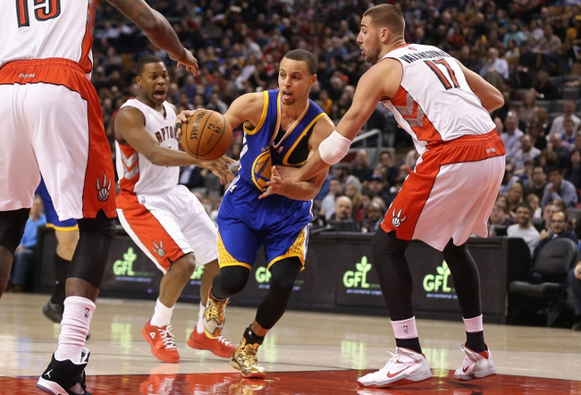 Mar 2, 2014; Toronto, Ontario, CAN; Golden State Warriors point guard Stephen Curry (30) goes to the basket against Toronto Raptors point guard Kyle Lowry (7) and center Jonas Valanciunas (17) at Air Canada Centre. The Raptors beat the Warriors 104-98. Mandatory Credit: Tom Szczerbowski-USA TODAY Sports