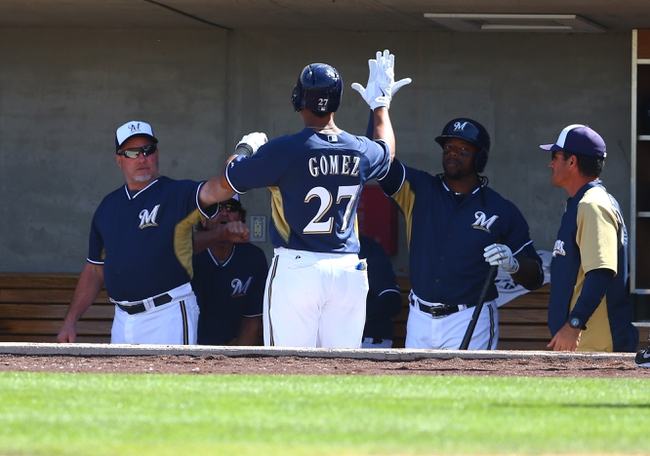 Mar 18, 2014; Phoenix, AZ, USA; Milwaukee Brewers outfielder Carlos Gomez (27) is congratulated by teammates after scoring in the fourth inning against the Texas Rangers at Maryvale Baseball Park. Mandatory Credit: Mark J. Rebilas-USA TODAY Sports