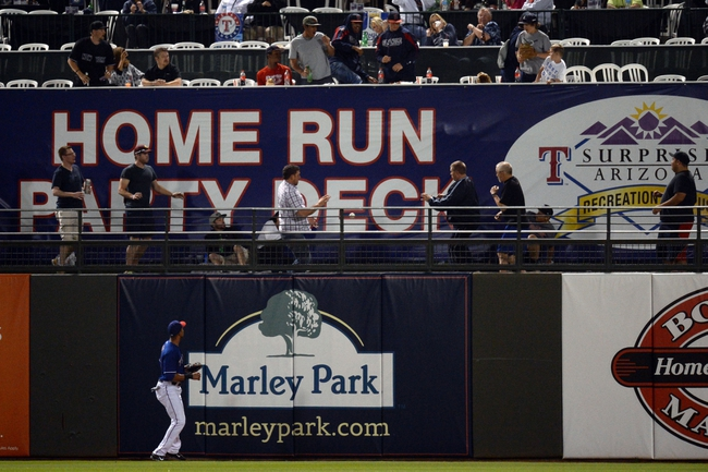 Mar 18, 2014; Surprise, AZ, USA; Texas Rangers right fielder Alex Rios (51) watches a home run ball by Chicago Cubs shortstop Javier Baez (not pictured) go over the wall in the third inning at Surprise Stadium. Mandatory Credit: Joe Camporeale-USA TODAY Sports