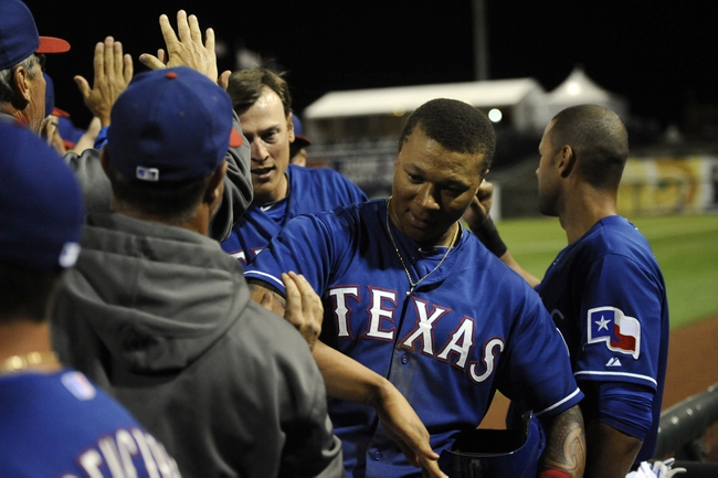 Mar 18, 2014; Surprise, AZ, USA; Texas Rangers center fielder Michael Choice (15) celebrates with teammates after hitting a game winning infield single in the tenth inning against the Chicago Cubs at Surprise Stadium. The Rangers won 7-6 in ten innings. Mandatory Credit: Joe Camporeale-USA TODAY Sports
