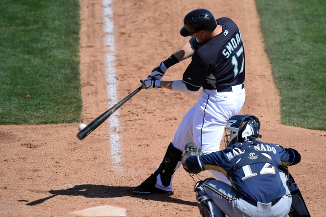 Mar 19, 2014; Peoria, AZ, USA; Seattle Mariners first baseman Justin Smoak (17) hits an RBI double in the third inning against the Milwaukee Brewers at Peoria Sports Complex. Mandatory Credit: Joe Camporeale-USA TODAY Sports