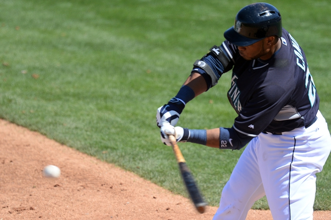 Mar 19, 2014; Peoria, AZ, USA; Seattle Mariners second baseman Robinson Cano (22) hits an RBI single in the third inning against the Milwaukee Brewers at Peoria Sports Complex. Mandatory Credit: Joe Camporeale-USA TODAY Sports