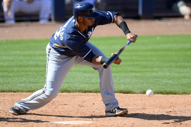 Mar 19, 2014; Peoria, AZ, USA; Milwaukee Brewers catcher Martin Maldonado (12) bunts in a run in the sixth inning against the Seattle Mariners at Peoria Sports Complex. The Brewers won 9-7. Mandatory Credit: Joe Camporeale-USA TODAY Sports
