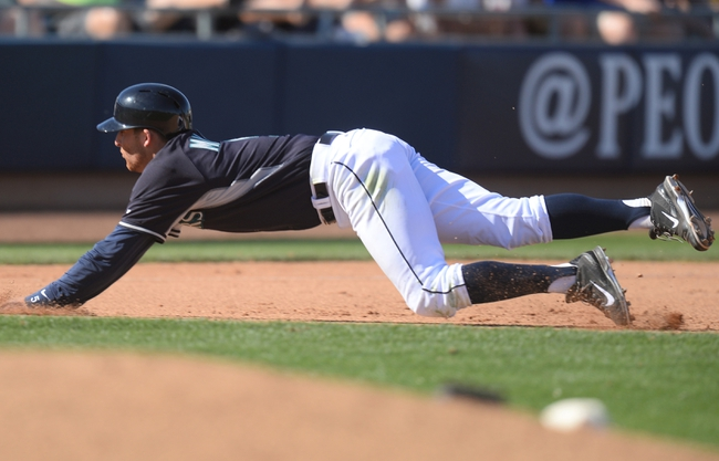 Mar 19, 2014; Peoria, AZ, USA; Seattle Mariners shortstop Brad Miller (5) slides into third after hitting a triple against the Milwaukee Brewers at Peoria Sports Complex. The Brewers won 9-7. Mandatory Credit: Joe Camporeale-USA TODAY Sports