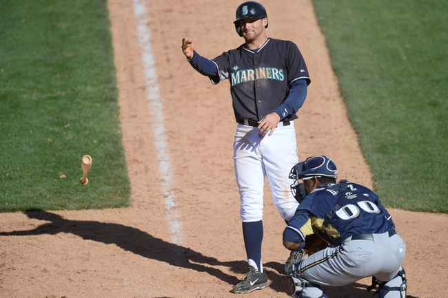 Mar 19, 2014; Peoria, AZ, USA; Seattle Mariners shortstop Brad Miller (5) throws his bat after drawing a walk in the ninth inning against the Milwaukee Brewers at Peoria Sports Complex. The Brewers won 9-7. Mandatory Credit: Joe Camporeale-USA TODAY Sports