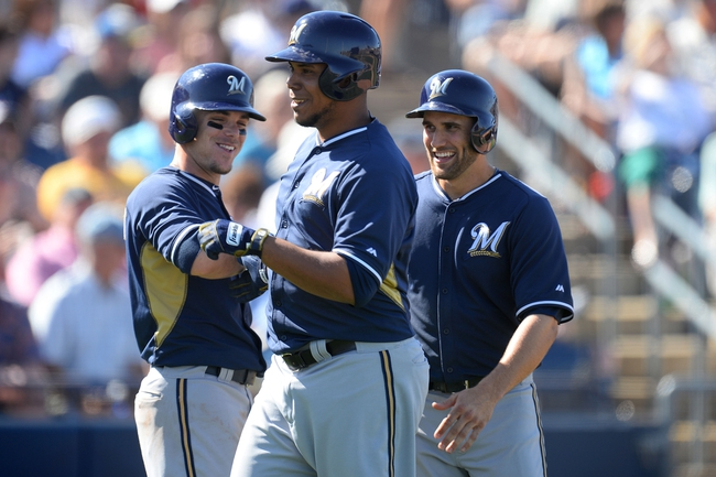 Mar 19, 2014; Peoria, AZ, USA; Milwaukee Brewers starting pitcher Wily Peralta (38) celebrates with Milwaukee Brewers second baseman Scooter Gennett (2) and Milwaukee Brewers third baseman Jeff Bianchi (14) after hitting a home run against the Seattle Mariners at Peoria Sports Complex. The Brewers won 9-7. Mandatory Credit: Joe Camporeale-USA TODAY Sports