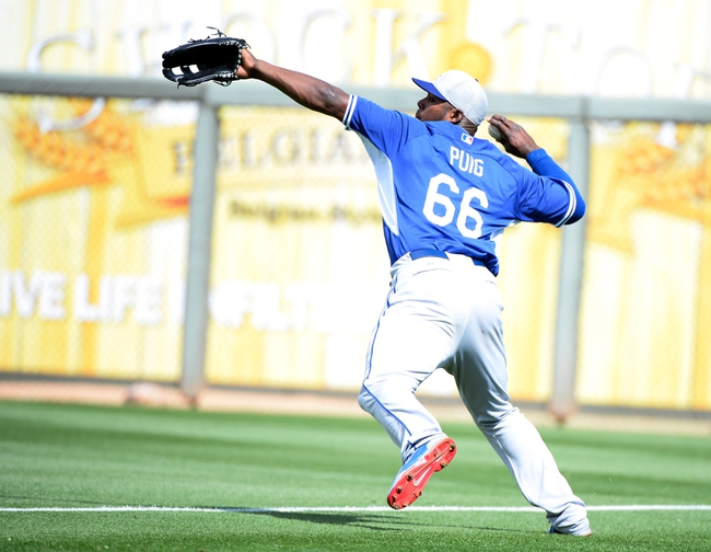 Mar 11, 2014; Surprise, AZ, USA; Los Angeles Dodgers right fielder Yasiel Puig (66) throws the ball after a catch during the fifth inning against the Kansas City Royals at Surprise Stadium. Mandatory Credit: Christopher Hanewinckel-USA TODAY Sports