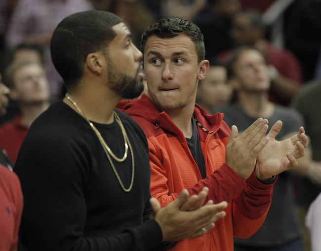 Mar 20, 2014; Houston, TX, USA; Houston Texans running back Arian Foster and Texas A&M quarterback Johnny Manziel sit court side during the second quarter of the game between Minnesota Timberwolves and the Houston Rockets at Toyota Center. Mandatory Credit: Andrew Richardson-USA TODAY Sports