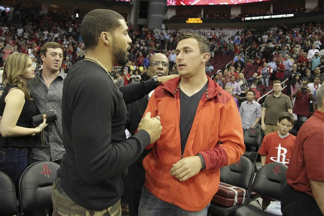 Mar 20, 2014; Houston, TX, USA; Houston Texans running back Arian Foster and Texas A&M quarterback Johnny Manziel shake hands following the fourth quarter of the game between the Minnesota Timberwolves and the Houston Rockets at Toyota Center. Mandatory Credit: Andrew Richardson-USA TODAY Sports