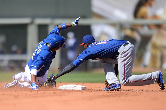 Mar 22, 2014; Surprise, AZ, USA; Kansas City Royals shortstop Alcides Escobar (2) slides into second base safely with a double while being tagged by Texas Rangers second baseman Jurickson Profar (13) at Surprise Stadium. Mandatory Credit: Joe Camporeale-USA TODAY Sports