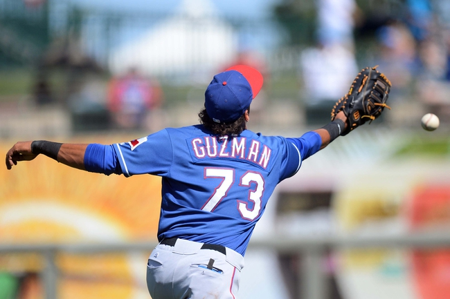 Mar 22, 2014; Surprise, AZ, USA; Texas Rangers infielder Ronald Guzman (73) is unable to track down a blooper in foul territory against the Kansas City Royals at Surprise Stadium. The Royals won 8-4. Mandatory Credit: Joe Camporeale-USA TODAY Sports