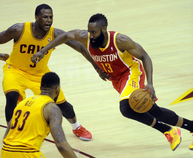 Mar 22, 2014; Cleveland, OH, USA; Houston Rockets guard James Harden (13) drives to the basket through Cleveland Cavaliers guard Dion Waiters (3) and forward Alonzo Gee (33) during the third quarter at Quicken Loans Arena. Houston won 118-111. Mandatory Credit: Ken Blaze-USA TODAY Sports