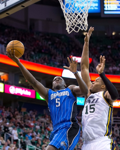 Mar 22, 2014; Salt Lake City, UT, USA; Orlando Magic guard Victor Oladipo (5) shoots against Utah Jazz center Derrick Favors (15) during the first half at EnergySolutions Arena. Mandatory Credit: Russ Isabella-USA TODAY Sports