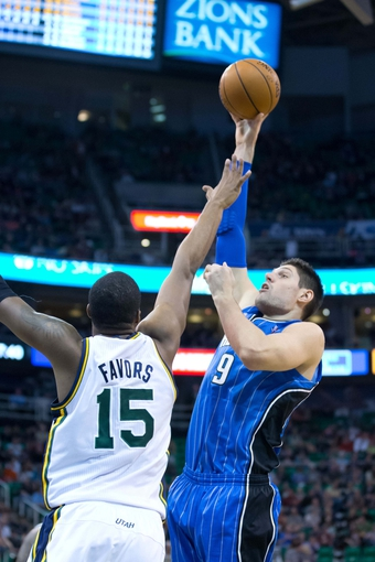 Mar 22, 2014; Salt Lake City, UT, USA; Orlando Magic center Nikola Vucevic (9) shoots over Utah Jazz center Derrick Favors (15) during the first half at EnergySolutions Arena. Mandatory Credit: Russ Isabella-USA TODAY Sports