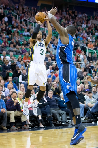 Mar 22, 2014; Salt Lake City, UT, USA; Utah Jazz guard Trey Burke (3) shoots against Orlando Magic forward Kyle O'Quinn (2) during the second half at EnergySolutions Arena. The Jazz won 89-88. Mandatory Credit: Russ Isabella-USA TODAY Sports