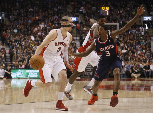 Mar 23, 2014; Toronto, Ontario, CAN; Toronto Raptors guard Nando De Colo (3) carries the ball against Atlanta Hawks guard Louis Williams (3) during the first half at the Air Canada Centre. Mandatory Credit: John E. Sokolowski-USA TODAY Sports
