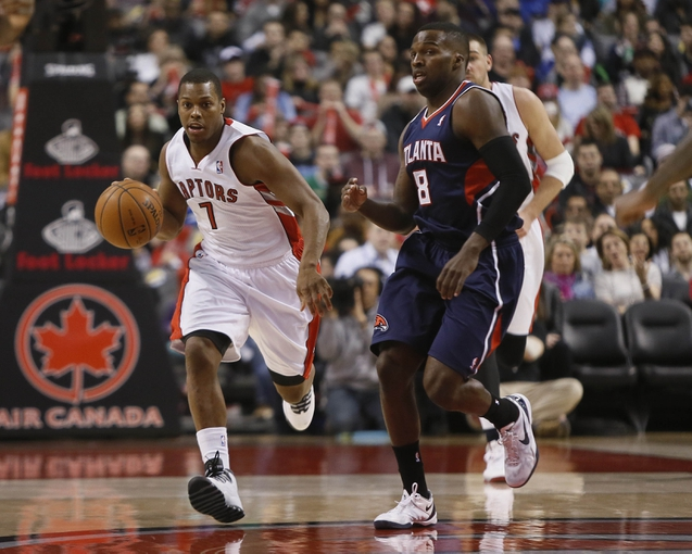 Mar 23, 2014; Toronto, Ontario, CAN; Toronto Raptors guard Kyle Lowry (7) dribbles past Atlanta Hawks guard Shelvin Mack (8) during the first half at the Air Canada Centre. Mandatory Credit: John E. Sokolowski-USA TODAY Sports
