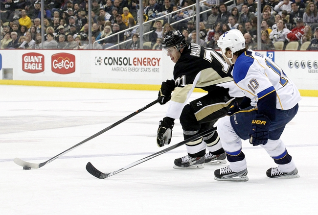 Mar 23, 2014; Pittsburgh, PA, USA; Pittsburgh Penguins center Evgeni Malkin (71) carries the puck as St. Louis Blues left wing Brenden Morrow (10) defends during the second period at the CONSOL Energy Center.  The St. Louis Blues won 1-0. Mandatory Credit: Charles LeClaire-USA TODAY Sports