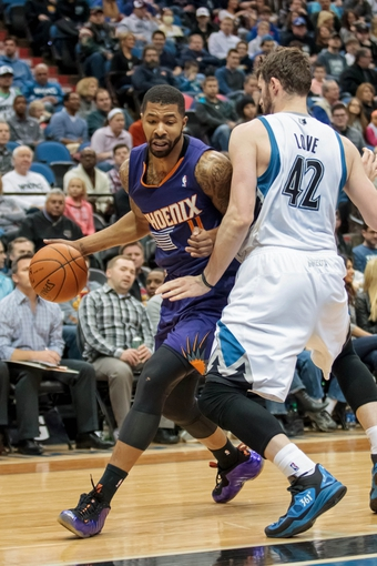 Mar 23, 2014; Minneapolis, MN, USA; Phoenix Suns forward Markieff Morris (11) dribbles in the second quarter against the Minnesota Timberwolves forward Kevin Love (42) at Target Center. Mandatory Credit: Brad Rempel-USA TODAY Sports