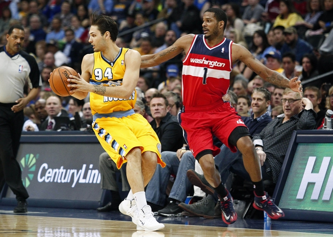 Mar 23, 2014; Denver, CO, USA; Denver Nuggets shooting guard Evan Fournier (94) keeps the ball in bounds under pressure from Washington Wizards small forward Trevor Ariza (1) in the first quarter at the Pepsi Center. Mandatory Credit: Isaiah J. Downing-USA TODAY Sports