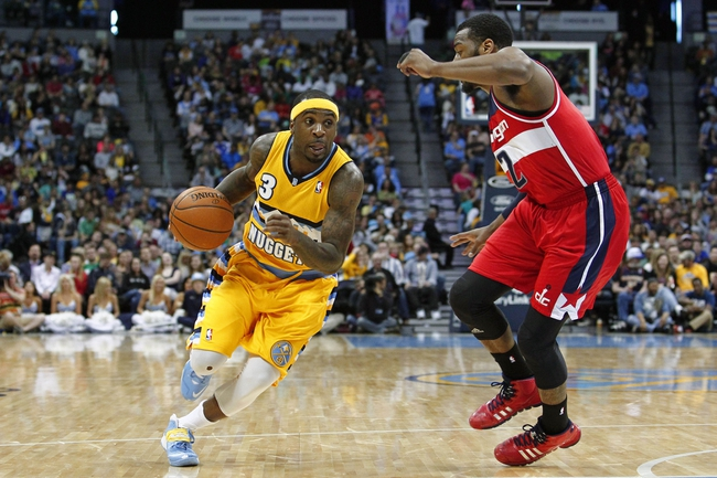 Mar 23, 2014; Denver, CO, USA; Washington Wizards point guard John Wall (2) guards Denver Nuggets point guard Ty Lawson (3) in the third quarter at the Pepsi Center. The Nuggets won 105-102. Mandatory Credit: Isaiah J. Downing-USA TODAY Sports