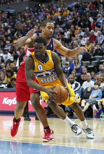 Mar 23, 2014; Denver, CO, USA; Denver Nuggets point guard Aaron Brooks (0) dribbles the ball in front of Washington Wizards point guard Andre Miller (24) in the fourth quarter at the Pepsi Center. The Nuggets won 105-102. Mandatory Credit: Isaiah J. Downing-USA TODAY Sports