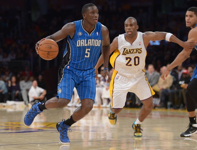Mar 23, 2014; Los Angeles, CA, USA; Orlando Magic guard Victor Oladipo (5) dribbles the ball as Los Angeles Lakers guard Jodie Meeks (20) chases at Staples Center. Mandatory Credit: Kirby Lee-USA TODAY Sports