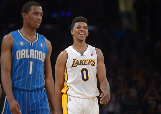 Mar 23, 2014; Los Angeles, CA, USA; Los Angeles Lakers guard Nick Young (0) smiles from the court in the fourth quarter as Orlando Magic guard Doron Lamb (1) looks on at Staples Center. The Lakers won 103-94. Mandatory Credit: Kirby Lee-USA TODAY Sports