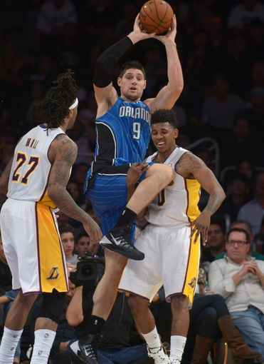 Mar 23, 2014; Los Angeles, CA, USA; Orlando Magic center Nikola Vucevic (9) looks to pass the ball as Los Angeles Lakers forward Jordan Hill (27) and guard Nick Young (0) defend at Staples Center. The Lakers won 103-94. Mandatory Credit: Kirby Lee-USA TODAY Sports