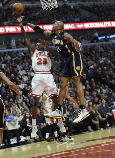 Mar 24, 2014; Chicago, IL, USA;  Chicago Bulls guard Tony Snell (20) is defended by Indiana Pacers forward David West (21) during the first half at the United Center. Mandatory Credit: David Banks-USA TODAY Sports